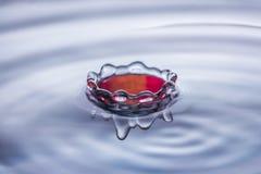 水下落在蓝色和红色口气的飞溅冠 免版税库存照片