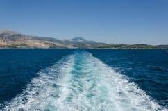 水乘一条巡航的小船追踪左 免版税库存图片