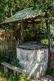 水井在位于村庄的屋顶下 免版税图库摄影
