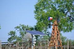 水井太阳与在夏天绿色树、农厂大农场篱芭和蓝天背景前面的得克萨斯风车 免版税库存照片