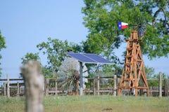 水井太阳与在夏天绿色树、农厂大农场篱芭和蓝天背景前面的得克萨斯风车 免版税库存图片