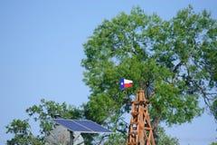 水井太阳与在夏天绿色树、农厂大农场篱芭和蓝天背景前面的得克萨斯风车 库存图片