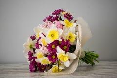 水仙,康乃馨,在桃红色和黄色颜色的菊花美丽的新鲜的开花的花束在灰色背景 库存照片