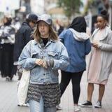 水兵和蓝色牛仔裤的一个女孩沿牛津街赶紧 免版税图库摄影