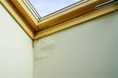 水和湿气损坏的天花板在屋顶窗口旁边 库存照片