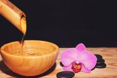 水喷气机从竹子倾吐入在一张木桌上的一个碗,在温泉治疗石头和兰花花旁边, 免版税图库摄影