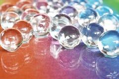 水在彩虹玻璃背景的胶凝体球 库存照片