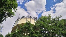 水塔,与手机帆柱,在与蓝天的树中 免版税库存图片