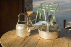 水壶和玻璃在木桌上 免版税库存图片