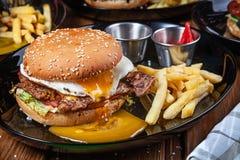 水多和鲜美汉堡用鸡蛋、莴苣和调味汁在一个黑色的盘子有薯条的 美国便当 与拷贝的汉堡包 免版税库存照片