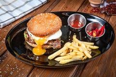 水多和鲜美汉堡用鸡蛋、莴苣和调味汁在一个黑色的盘子有薯条的 美国便当 与拷贝的汉堡包 库存图片