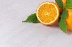 水多的切片桔子特写镜头和整个桔子与绿色叶子在白色木板 图库摄影