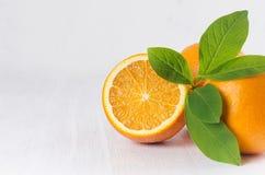 水多的切片桔子特写镜头和整个桔子与绿色叶子在白色木背景 免版税库存照片