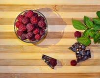 水多的新鲜的莓莓果说谎在碗和在与巧克力绿色叶子和片断,顶视图的一张桌上 免版税库存照片