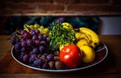 水多的果子的分类在一块板材的在木桌上 图库摄影