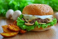 水多的汉堡用牛肉砍,乳酪,蘑菇,沙拉 在新鲜蔬菜和芯片中的桌上 库存照片