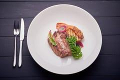 水多的牛排用土豆和沙拉在白色板材 免版税库存图片