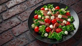 水多的牛肉牛腰肉排沙拉用烤蕃茄、希腊白软干酪和绿色菜在一个黑色的盘子 健康的食物 免版税库存照片