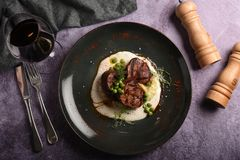 水多的猪肉大奖章、服务用绿豆和迷迭香小树枝在板材 猬 库存照片