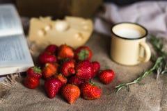 水多的红色草莓的一个大客人在被装饰的织品说谎 Masdaam乳酪、hurbs、一本开放书和葡萄酒杯子 免版税图库摄影