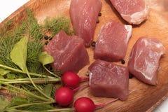 水多的肉片在有调味料、草本和菜的一块木板材服务 免版税图库摄影