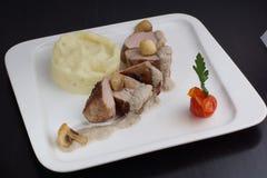 水多的里脊肉,洒与坚果调味汁用在一块板材的蘑菇用土豆泥 免版税库存图片