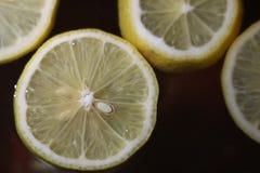 水多的黄色柠檬在黑暗的背景的水中 免版税图库摄影