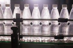 水工厂-处理和装瓶的纯净的泉水水瓶线入小瓶 库存照片
