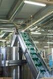 水工厂-处理和装瓶的纯净的泉水水瓶线入小瓶 免版税图库摄影