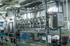 水工厂-处理和装瓶的纯净的泉水水瓶线入小瓶 库存图片