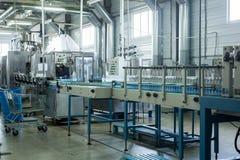 水工厂-处理和装瓶的纯净的泉水水瓶线入小瓶 免版税库存照片