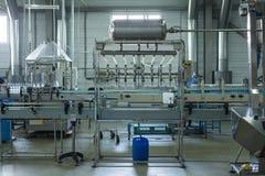 水工厂-处理和装瓶的纯净的泉水水瓶线入小瓶 图库摄影