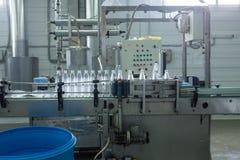 水工厂-处理和装瓶的纯净的泉水水瓶线入小瓶 免版税库存图片