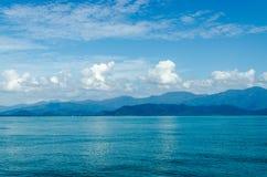 水平海景包括森林山、水蓝天和波浪  免版税库存图片