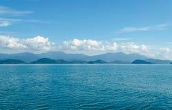 水平海景包括森林山、水蓝天和波浪  库存照片