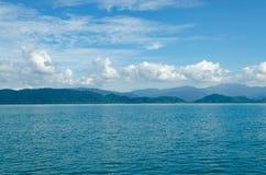 水平海景包括森林山、水蓝天和波浪  免版税库存照片