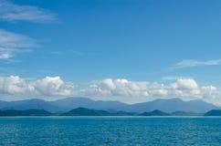 水平海景包括森林山、水蓝天和波浪  图库摄影