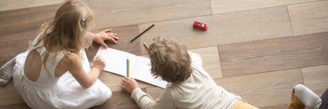 水平的上面画在温暖的木地板上的看法小孩 免版税库存照片