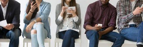 水平的坐在行的图象多种族人民使用电子设备 库存图片