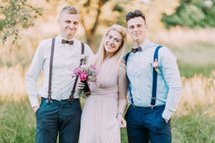 水平的照片两个现代穿戴了最佳的人和女傧相有桃红色花束的在背景  库存照片