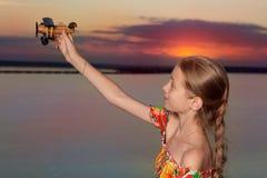 水库的背景的女孩,举了她的有玩具飞机的,梦想,红色日落,长途旅行的概念手 库存照片