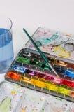 水彩与画笔和水玻璃的油漆配件箱 免版税库存图片