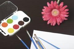 水彩和刷子黑暗的表面上 附近在一个花瓶的一棵人造花静物画的 创造性的主题 免版税库存图片