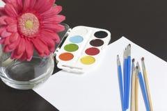 水彩和刷子黑暗的表面上 附近在一个花瓶的一棵人造花静物画的 创造性的主题 库存图片