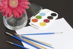 水彩和刷子黑暗的表面上 附近在一个花瓶的一棵人造花静物画的 创造性的主题 免版税图库摄影