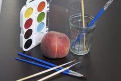 水彩和刷子黑暗的表面上 附近静物画的一个桃子 创造性的主题 免版税图库摄影
