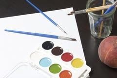 水彩和刷子黑暗的表面上 附近静物画的一个桃子 创造性的主题 库存图片