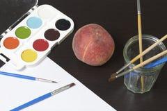 水彩和刷子黑暗的表面上 附近静物画的一个桃子 创造性的主题 免版税库存图片