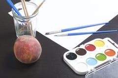 水彩和刷子黑暗的表面上 附近静物画的一个桃子 创造性的主题 库存照片