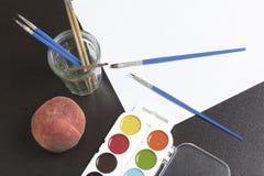 水彩和刷子黑暗的表面上 附近静物画的一个桃子 创造性的主题 免版税库存照片